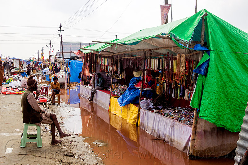 flooded market stalls - kumbh mela 2013 (india), flood, flooded, hindu pilgrimage, hinduism, india, maha kumbh mela, man, merchant, shopkeeper, sitting, souvenir shop, stalls, street market, street seller, tarp, vendor