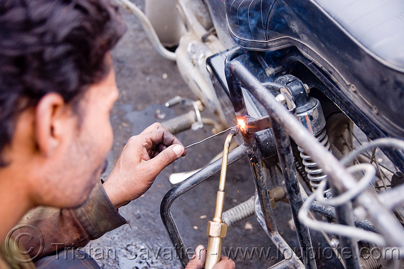 getting my cracked rack welded (again) - leh (india), fixing, ladakh, luggage rack, man, motorbike touring, motorcycle touring, repairing, road, royal enfield bullet, welder, welding, worker, working