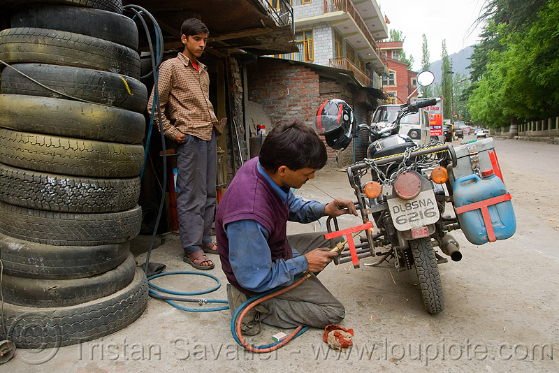 getting my cracked rack welded - manali (india), 500cc, bald tires, fixing, india, luggage rack, man, manali, mechanic, motorcycle touring, repairing, road, royal enfield bullet, tire stack, user tired, welder, welding torch, worker, working