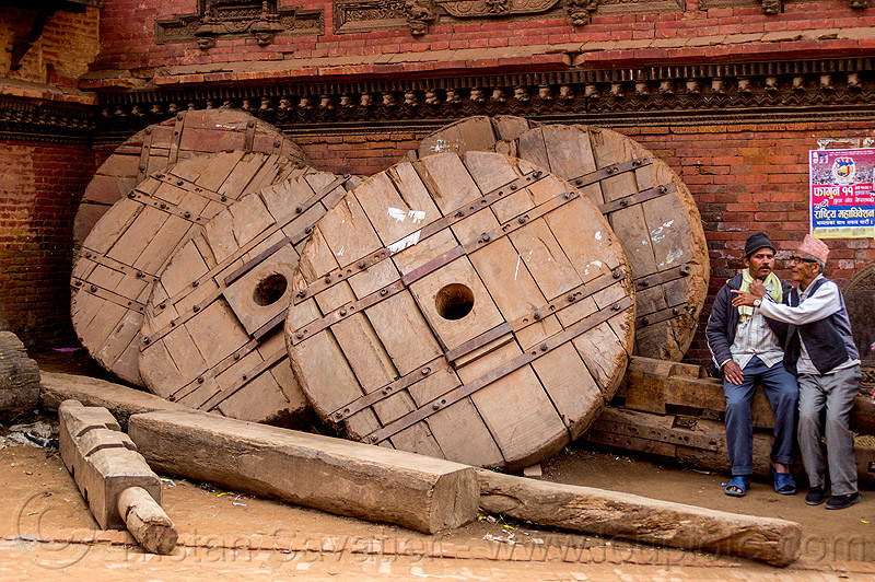 giant wooden wheel of the bhairab chariot used during the bisket jatra festival - bhaktapur  (nepal), bhaktapur, men, standing, tachupal tole, wooden wheels
