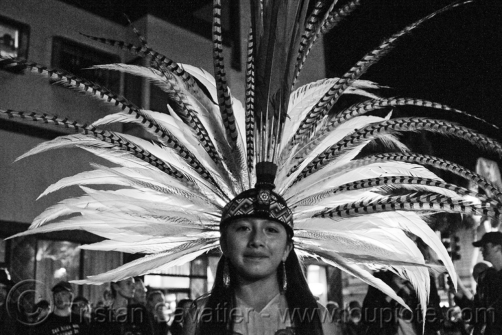 girl in aztec dancer traditional costume - feather headdress - dia de los muertos - halloween (san francisco), aztec costume, backlight, dancer, day of the dead, dia de los muertos, face painting, facepaint, feather headdress, feather headwear, feathers, halloween, makeup, night, woman