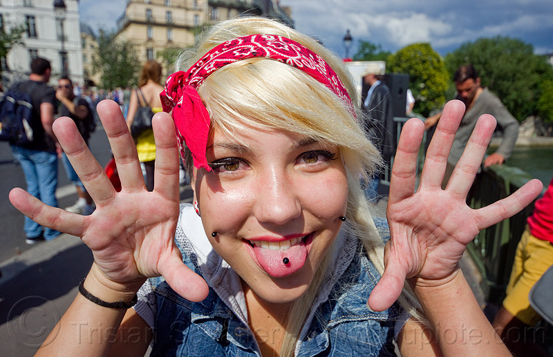 girl with tongue piercing, bandana, blonde, cheek piercing, festival, gay pride, hair band, hands, paris, people, red, red bandana, red bandanna, sticking out tongue, sticking tongue out, stickink out tongue, woman