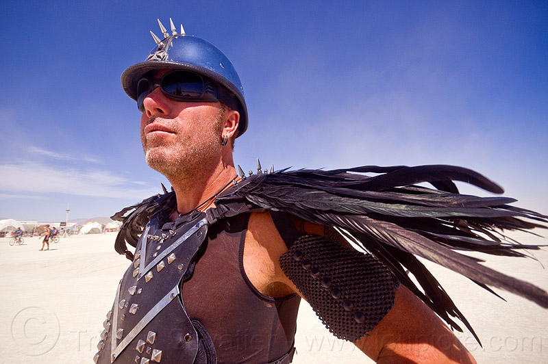 gladiator costume with black feathers - burning man 2012, black feathers, gladiator costume, helmet, spikes, unshaven man