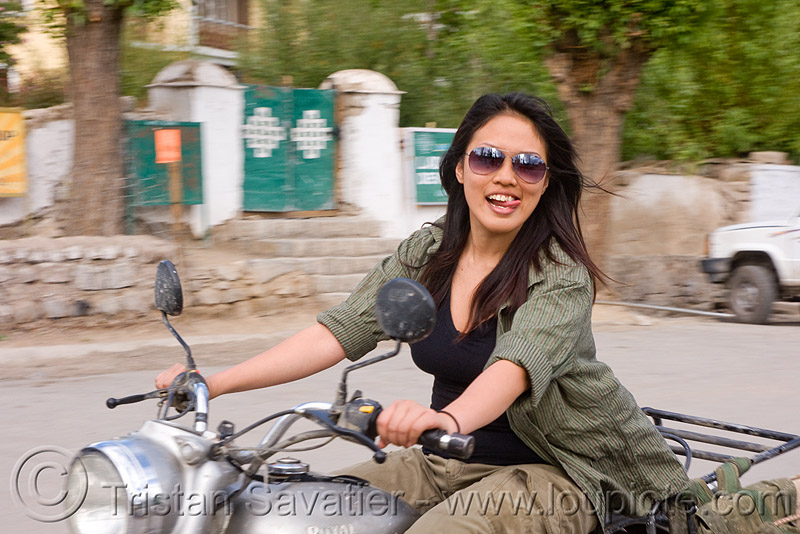 grace - woman riding royal enfield bullet motorcycle - leh (india), 350cc, ladakh, motorbike, motorbike touring, motorcycle touring, motorcyclist, people, rider, sticking out tongue, sticking tongue out, street