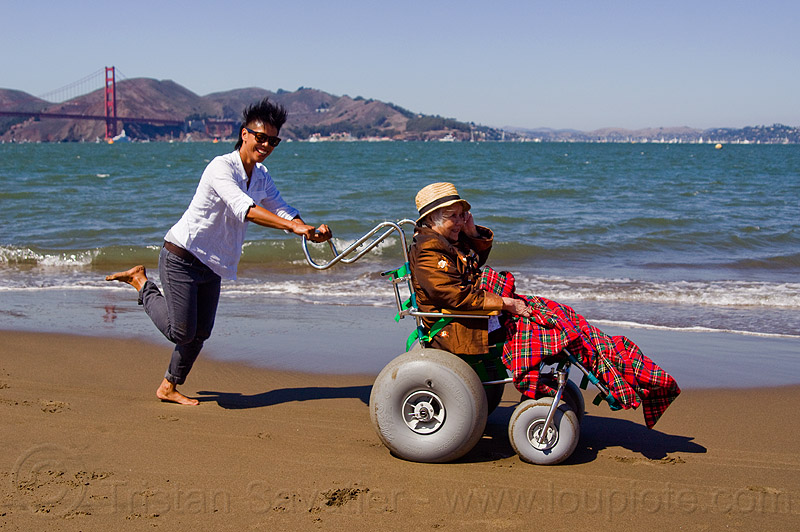 grandma on beach wheelchair with granddaughter running on the beach, blanket, chinese, crissy field, crissy field beach, family, grandmother, happy, hat, jenn, ocean, old, old woman, people, pushing, rolling, sand, sea, senior, straw hat, water, women