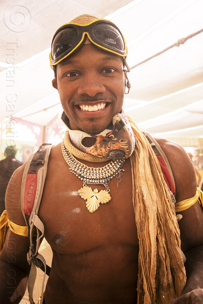 handsome man at center camp - burning man 2015, burning man, center camp, goggles, metal necklaces