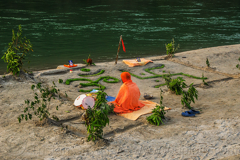 hindu devotee meditating - om and swastika symbols (india), baba, beach, ganga river, ganges river, garden, grass, hinduism, man, meditating, meditation, om, orange, rishikesh, sand, sitting, swastika, water