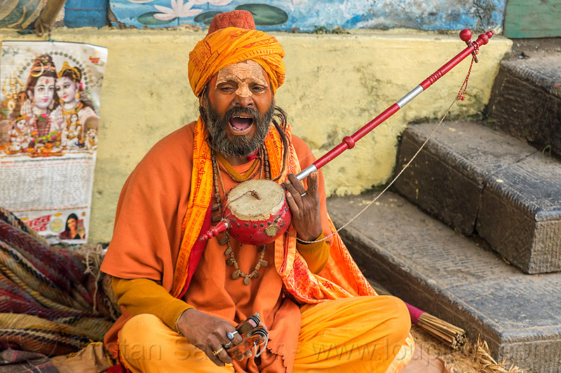 hindu devotee singing mantra and playing musical instrument (nepal), baba, beard, bhagwa, cross-legged, hindu, hinduism, kathmandu, maha shivaratri, man, musical instrument, pashupatinath, playing music, sadhu, saffron color, singing, sitting, tilak
