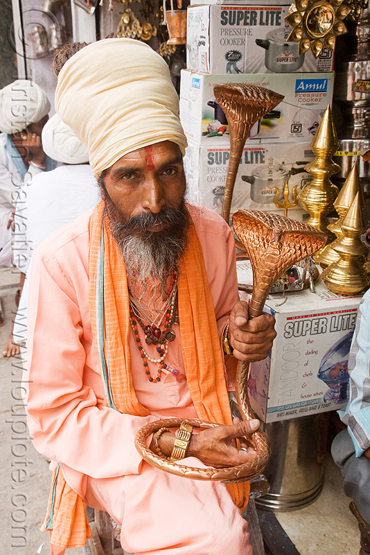 hindu holy man shopping for a cobra sculpture for his temple - udaipur (india), baba, beard, brass, cobra, guru, hindu holy man, hinduism, india, priest, sadhu, sculpture, shop, snake