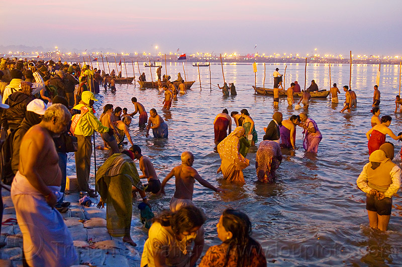 hindu pilgrims bathing in the ganges river at sangam - kumbh mela 2013 (india), crowd, dawn, fence, ganga river, ganges river, hindu, hinduism, holy bath, holy dip, kumbha mela, maha kumbh mela, men, paush purnima, pilgrims, reflections, ritual bath, river bath, river bathing, river boats, street lights, triveni sangam, water, women, yatris