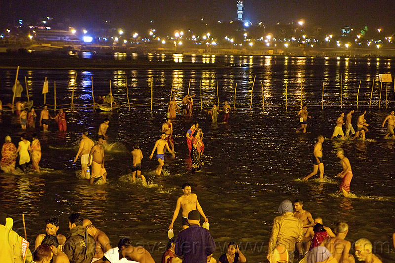 hindu pilgrims bathing in the ganges river at sangam at night - kumbh mela 2013 (india), crowd, fence, ganga river, ganges river, hindu, hinduism, holy bath, holy dip, kumbha mela, maha kumbh mela, men, night, paush purnima, pilgrims, reflections, ritual bath, river bath, river bathing, street lights, triveni sangam, water, women, yatris