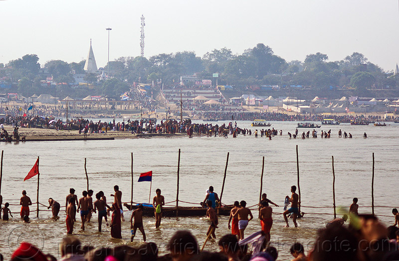 hindu pilgrims on sand bar in the ganges river at sangam - kumbh mela 2013 (india), crowd, dawn, fence, flags, ganga, ganges river, hindu pilgrimage, hinduism, holy bath, holy dip, india, maha kumbh mela, nadi bath, paush purnima, pilgrims, ritual bath, river bank, river bathing, river boats, river island, sand bar, silhouettes, triveni sangam