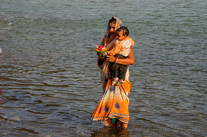 hindu woman and small child in ganges river with offering (india), baby, child, ganga, ganges river, ghats, hinduism, holy bath, holy dip, india, kid, mother, nadi bath, offering, rishikesh, river bathing, saree, sari, standing, toddler, triveni ghat, wading, woman