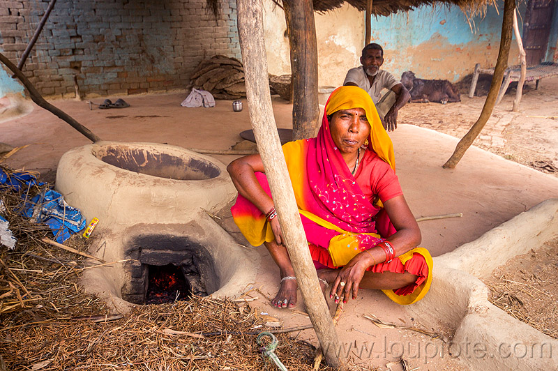 indian woman sitting near mud stove, adobe floor, earthen floor, fireplace, khoaja phool, kitchen, man, sari, sitting, village, woman, wood stove, खोअजा फूल