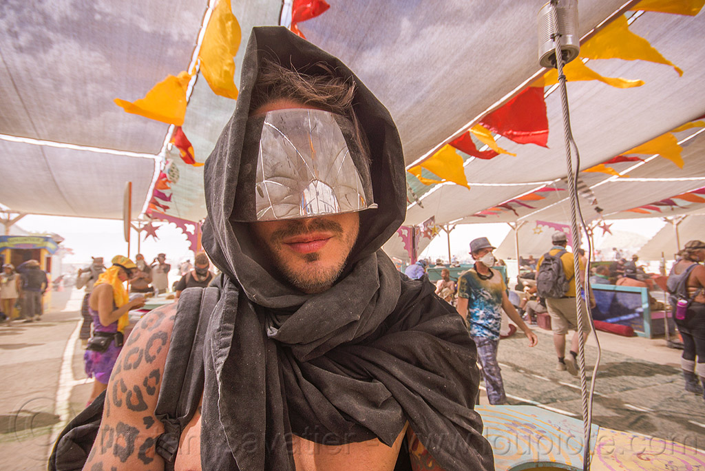 hooded man with mirror visor at center camp - burning man 2015, arm tattoo, burning man, center camp, cheetah pattern tattoo, cheetah tattoo, eric flores, hood, hooded, mirror visor, reflection