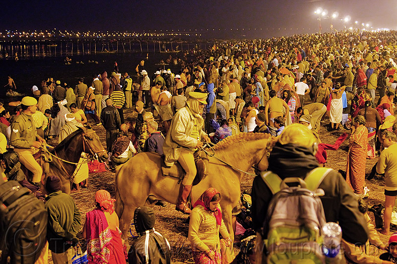 horse police patrolling the crowd of hindu pilgrims gathering at kumbh mela 2013 (india), cops, crowd control, fence, ganga, ganges river, hindu pilgrimage, hinduism, holy dip, horse riding, horseback riding, india, law enforcement, maha kumbh mela, men, mounted police, night, paush purnima, pilgrims, police horses, police officers, river bank, street lights, triveni sangam, women