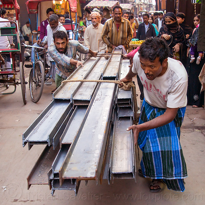 I-beam steel rails rolled on cart in street (india), construction, crowd, delhi, i-beams, market, men, pushing, rope, roped, steel beams, street, workers
