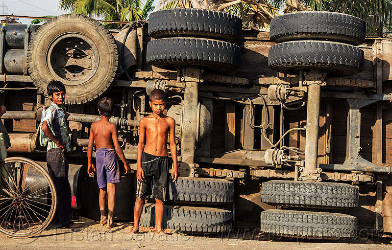 indian boys near underbelly of overturned truck (india), boys, children, crash, lorry, overturned truck, road, rollover, standing, tata motors, traffic accident, truck accident, underbelly, wheels, wreck