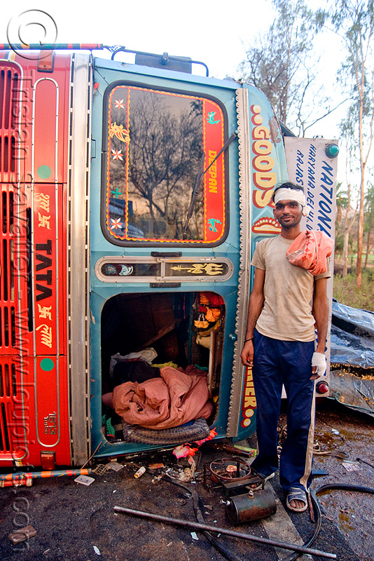indian truck driver and his overturned truck - accident (india), cab, cabin, crash, lorry, man, people, road, rollover, standing, swastika, tata, tata motors, traffic accident, truck accident, trucker, wreck