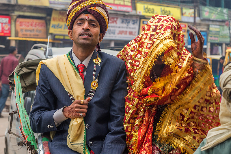 indian wedding, proud groom holding his covered bride like a trophy
