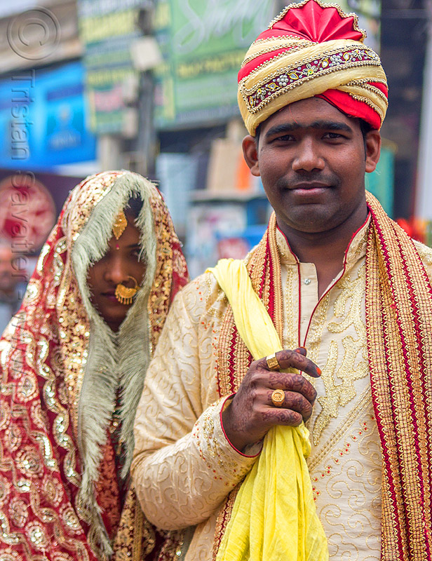 indian wedding - proud indian groom with turban holding bride in tow like a trophy (india), bride, dressed-up, gold jewelry, groom, hand mehndi, headdress, india, indian wedding, man, nose piercing, nostril piercing, piercing jewelry, scarf, standing, traditional, turban, varanasi, woman