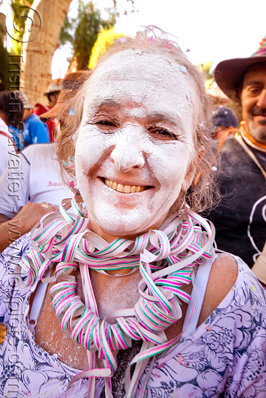 indigenous woman with white talk powder and serpentine throws - carnaval de tilcara (argentina), andean carnival, noroeste argentino, quebrada de humahuaca