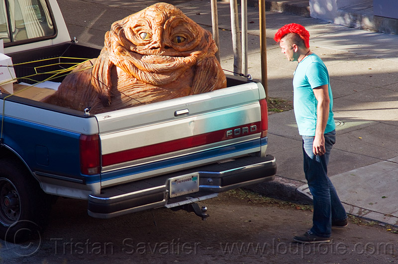 jabba the hutt in a pickup truck, character, giant muppet, jabba the hutt, man, mohawk hair, pickup truck, punk, red mohawk, special effects, starwars, street