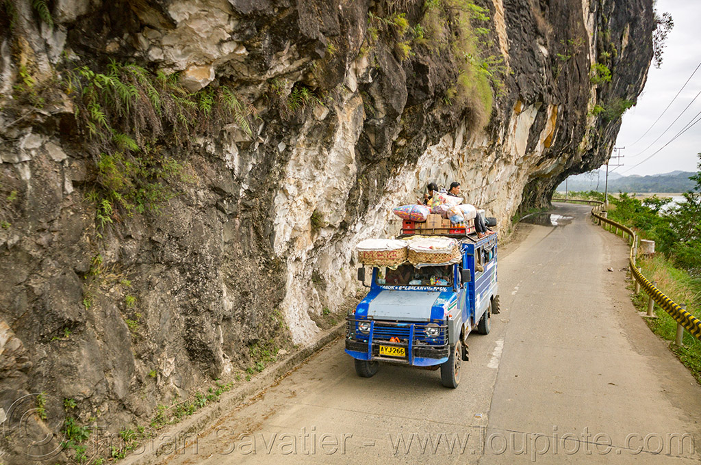 jeepney on road with overhanging cliff (philippines), cliff, cordillera, jeepney, overhanging rock, passengers, philippines, road, roof, sitting