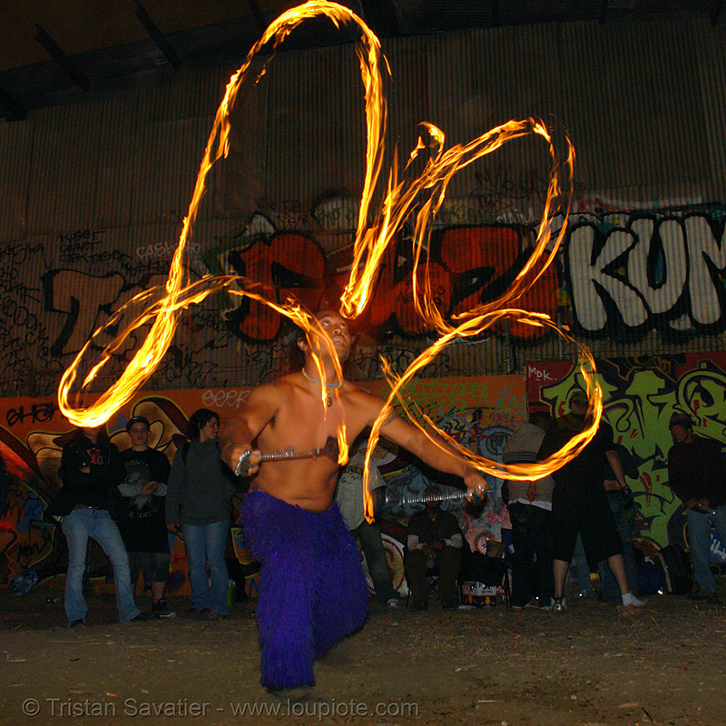 john-paul spinning fire poi (san francisco), fire dancer, fire dancing, fire performer, fire spinning, flames, graffiti, industrial, long exposure, night, people, toxic beach, warehouse