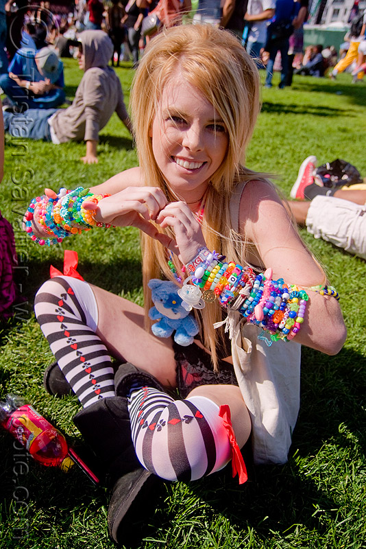 kandi kid with cuffs making heart sign, beads, blonde, clothing, cross-legged, fashion, heart sign, kandi bracelets, kandi cuffs, kandi kid, kandi raver, lovevolution, sitting, woman
