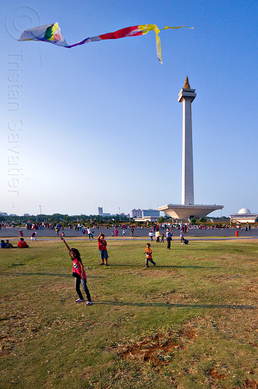 kid flying a kite near the national monument (monas) in jakarta, architecture, children, column, eid ul-fitr, flying, girl, jakarta, java, kids, kite, medan merdeka, merdeka square, monas, monumen nasional, national monument, park, turf