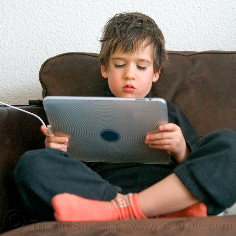 kid playing video game on iPad, boy, child, coach, cross-legged, ipad, kid, playing, sitting, tablet computer, video game