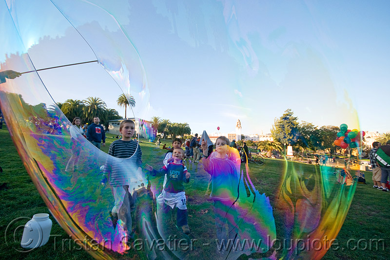 kids behind giant soap bubble, big bubble, children, giant bubble, iridescent, playing, turf