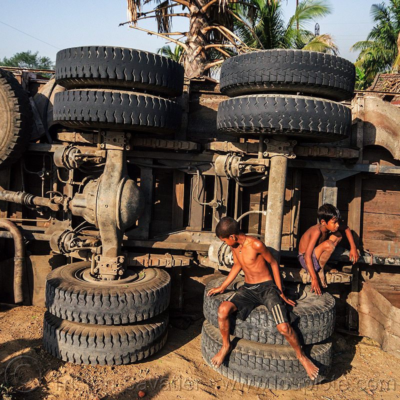 kids playing on overturned truck (india), boys, children, crash, dead axle, differential, india, kids, lorry, overturned truck, playing, road, rollover, sitting, tata motors, traffic accident, truck accident, underbelly, wreck