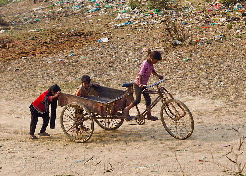 kids playing with freight tricycle (india), boy, cargo tricycle, cargo trike, children, environment, freight trike, garbage, girl, people, plastic, plastic trash, pollution, pushing, riding, rubbish