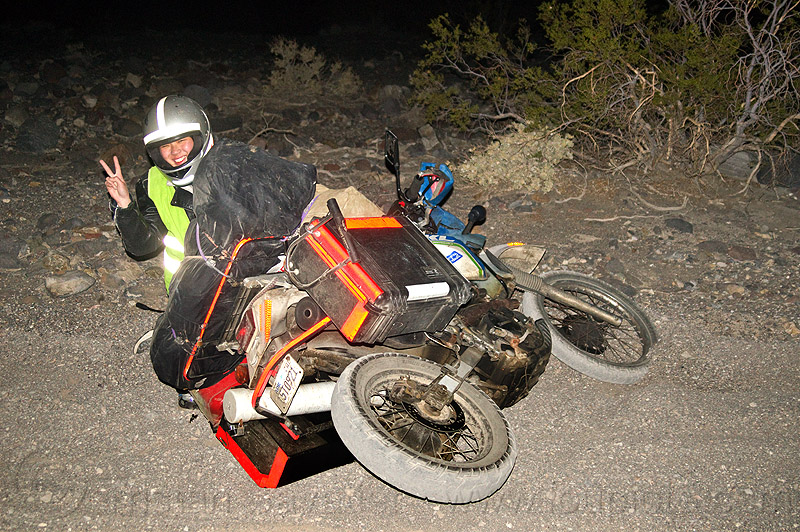 KLR 650 motorbike crash, accident, desert, dirt road, dropped, dual-sport, helmet, kawasaki, luggage rack, lying down, mishap, motorbike touring, motorcycle, motorcycle accident, motorcycle helmet, motorcycle touring, night, pannier cases, panniers, peace sign, people, reflective tape, sand, sharon, unpaved, v sign, woman