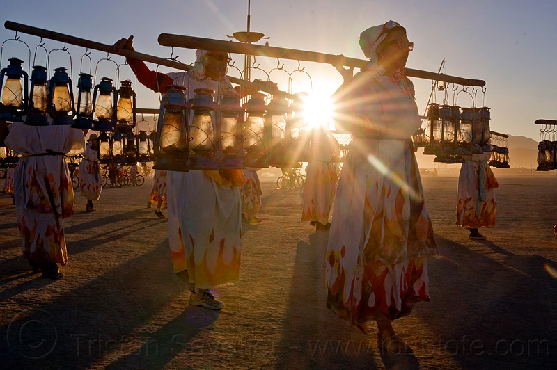 lamplighters at sunset - burning man 2012, backlight, dawn, flare, lamp lighters, lamplighter, lamps, lanterns, lens flare, people, petrol lamps, petrol lanterns, poles, sun