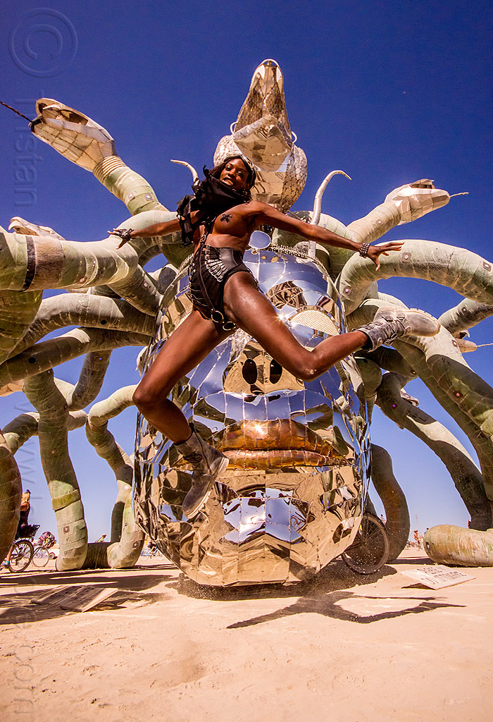 layla jumping in front of medusa - burning man 2015, art installation, burning man, head, jump, jumpshot, kevin clark, medusa madness, metal, sculpture, snakes, steel, woman
