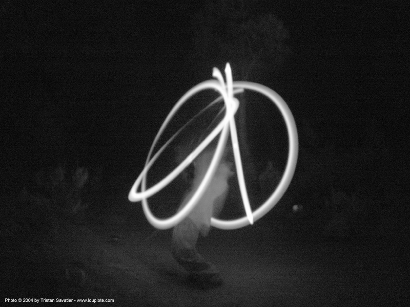 light-dancer-drawing-peace-sign - rainbow gathering - hippie, fire dancer, fire dancing, fire performer, fire poi, fire spinning, flames, hippie, long exposure, night, rainbow family, rainbow gathering, spinning fire