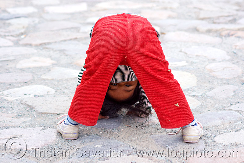 little girl playing (argentina), argentina, child, cobblestones, iruya, kid, little girl, noroeste argentino, playing, quebrada de humahuaca, upside-down