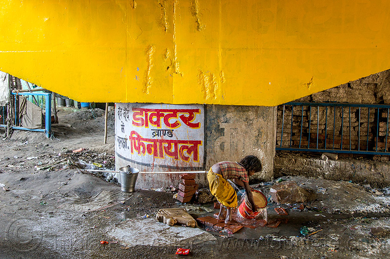 little girl rinsing bucket at water hose, bridge pillar, child, daraganj, kid, kumbh mela, kumbha mela, maha kumbh mela, metal bucket, people, pipe, piping, plastic, plastic pipe, plastic piping, steel bucket, water pipe
