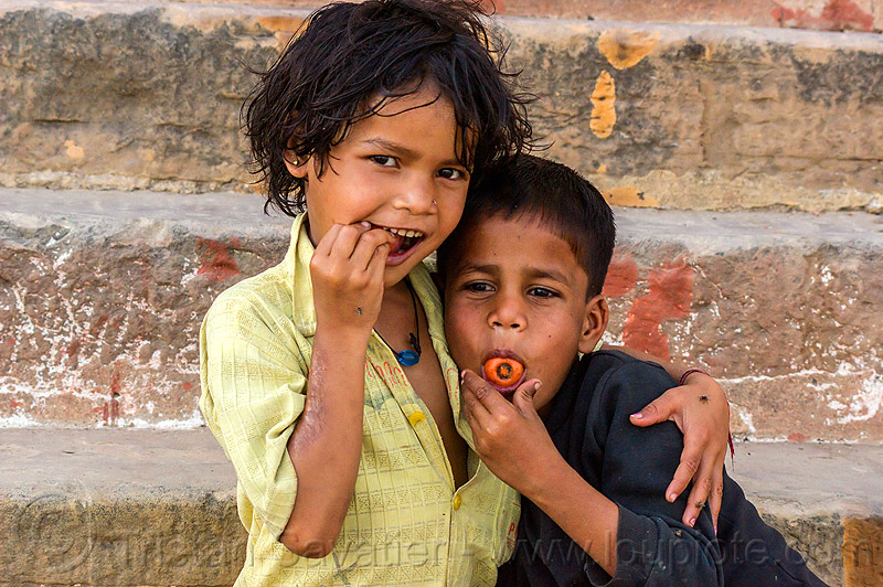 little girl with her brother - eating carrots (india), boy, brother, carrot, children, eating, hug, hugging, kids, little girl, siblings, varanasi