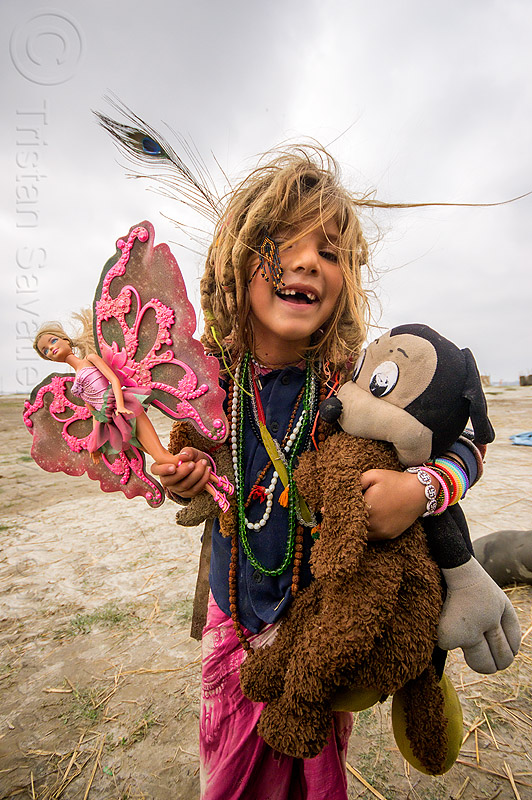 little hippie girl with pink butterfly barbie doll - ilita, baby teeth, barbie butterfly, barbie doll, blonde, child, hindu pilgrimage, hinduism, hippie, ilita, india, kid, little girl, maha kumbh mela, mickey mouse doll, missing teeth, necklaces, peacock feather, pink butterfly wings, teddybear, toys