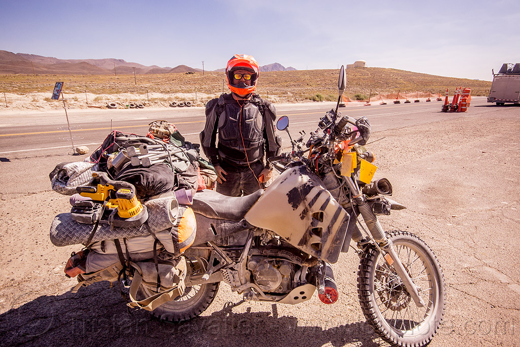 loaded KLR 650 motorcycle - burning man 2015, bags, burning man, dual-sport, dust, dusty, helmet, ims tank, kawasaki, klr 650, luggage, motorbike touring, motorcycle touring, overloaded, rider, road, standing