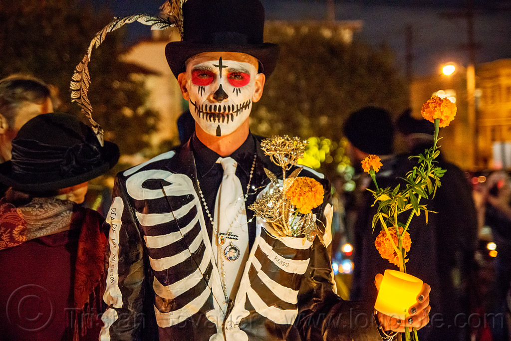 man in skeleton costume - black suit and hat - dia de los muertos, black suit, candle light, day of the dead, dia de los muertos, face painting, facepaint, feather, halloween, man, marigold flowers, necklace, night, skeleton costume, skeleton suit, skull makeup, stovepipe hat, white tie
