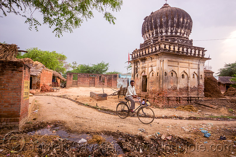 man on bicycle near old monument in indian village, bicycle, garbage, india, khoaja phool, man, monument, plastic trash, shrine, village, खोअजा फूल