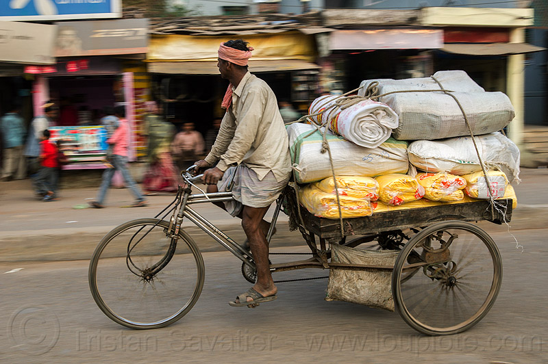 man riding freight tricycle (india), bags, bearer, cargo, cargo tricycle, cargo trike, freight trike, load, moving, people, sacks, street, transport, transportation, transporting, varanasi