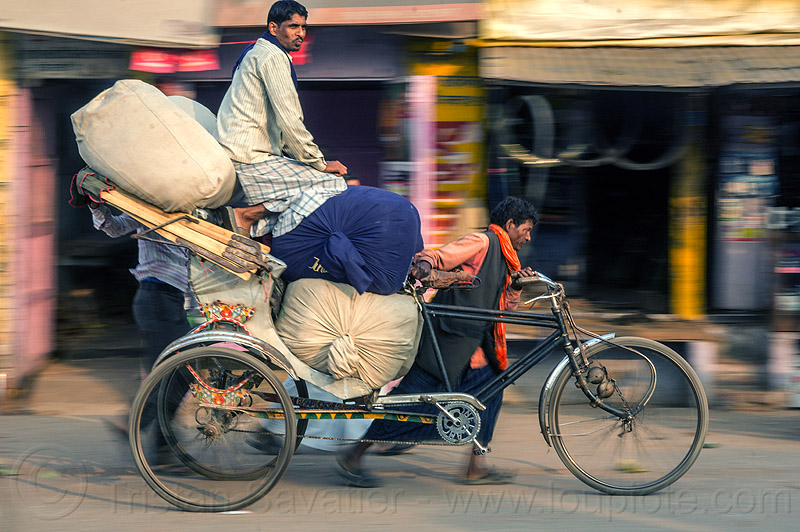 man sitting on top of large sacks on cycle rickshaw (india), bags, cargo, cycle rickshaw, freight, heavy, india, load, men, moving, sacks, sitting, transport, transportation, transporting, varanasi, walking