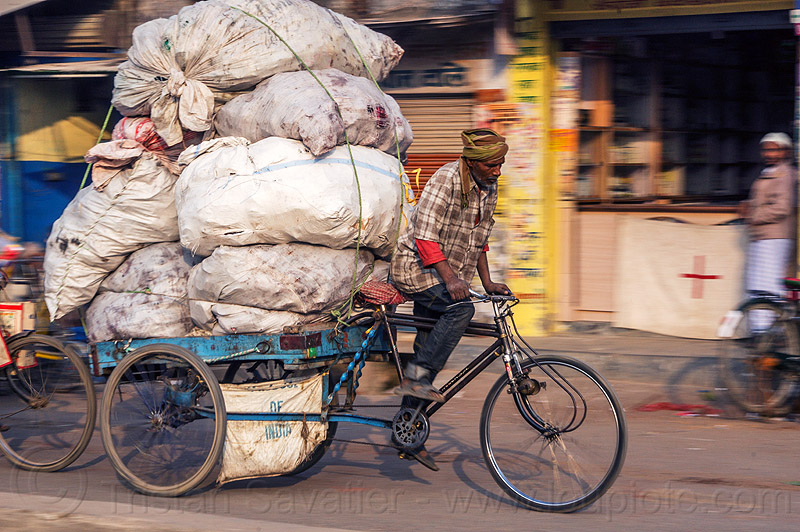 man transporting large load of freight on tricycle (india), bags, bearer, cargo tricycle, cargo trike, freight tricycle, freight trike, heavy, load, man, moving, riding, sacks, street, transport, transportation, transporting, varanasi