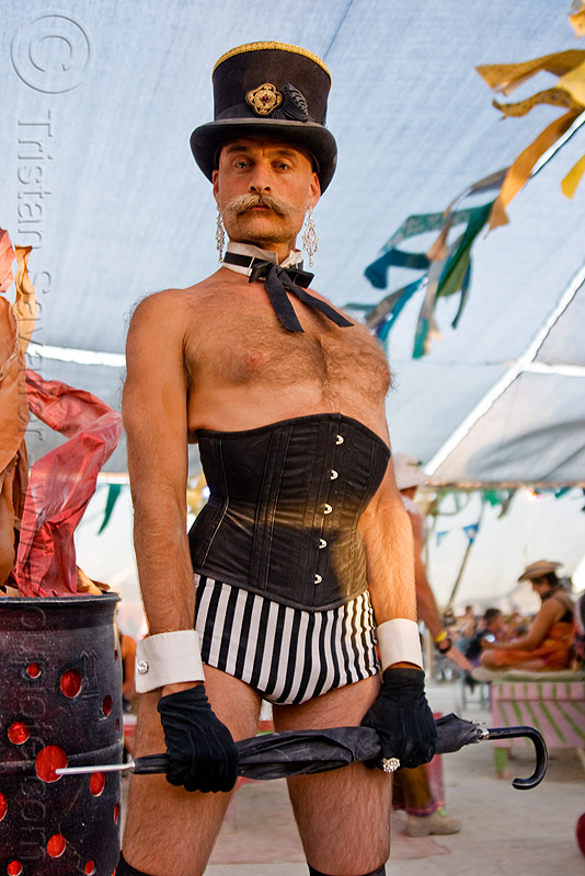 man with corset, bow tie, burning man, center camp, corset, dickie bow, fashion show, moustache, mustache, randal smith, stovepipe hat, umbrella